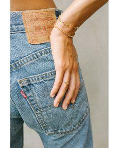 シンプルな18kゴールドメッキのチェーンブレスレットをつけた女性