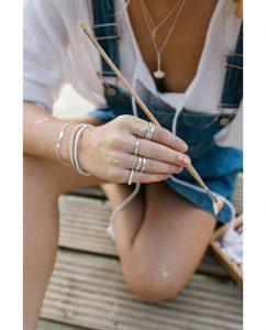 ハンドメイドならではの丸いフォルムがキュートなシンプルなダイヤモンドを埋め込んだスターリングシルバー925のリングをつけた女性