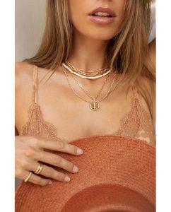 白とゴールドのビーズがキュートなネックレスをつけた女性