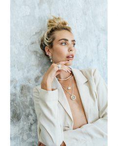 白とシルバーのビーズがキュートなネックレスをつけた女性