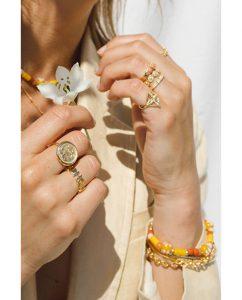 コインにヤシの木があしらわれた18kゴールドメッキのリングをつけた女性