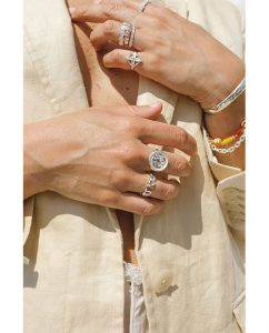 コインにヤシの木があしらわれたスターリングシルバー925のリングをつけた女性