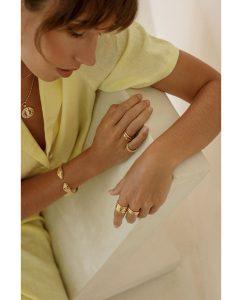 ハンドメイドならではの丸いフォルムがキュートなシンプルな18kゴールドメッキのリングをつけた女性