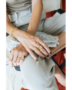 スカラベのモチーフ付き18kゴールドメッキのピンキーリングをつけた女性