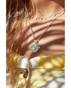 キュートなチャーム付きのシルバー925のネックレスをつけた女性