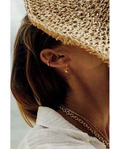 18kゴールドメッキのヴィンテージな雰囲気漂う桃がモチーフのチャーム付きフープピアスをつけた女性