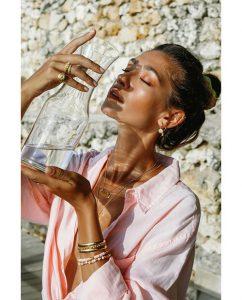 太陽がモチーフの18kゴールドメッキのピンキーリングをつけた女性