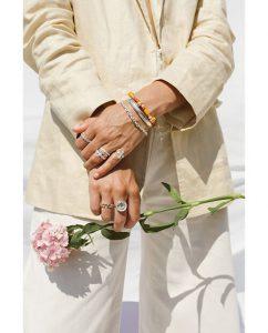 シルバー925のヤシの木モチーフのピンキーリングをつけてお花を持った女性