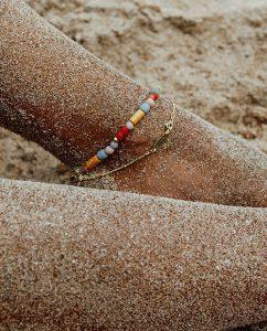 シンプルなゴールドのアンクレットをつけた海辺の人