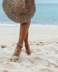 ブルーと赤のリサイクルビーズのハンドメイドのアンクレットをつけた海辺の女性