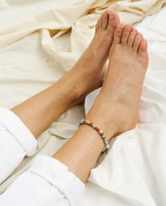 ブルーと赤のリサイクルビーズのハンドメイドのアンクレットをつけた女性の足