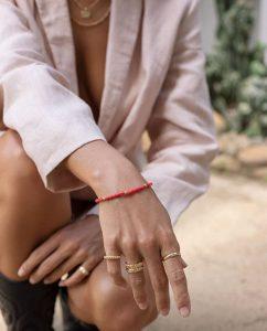 サンゴのような紅いビースがキュートなブレスレットをつけた女性