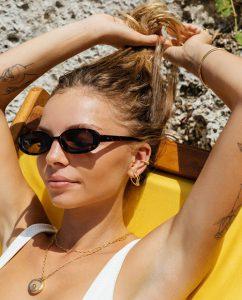海辺でゴールドのスタッドピアスをつけた女性