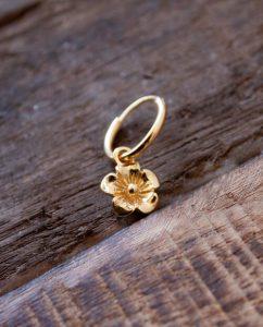 揺れるお花のチャームがついたゴールドのフープピアス