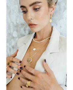 シンプルな18kゴールドメッキのラウンドネックレスを重ね付けしたビキニの女性
