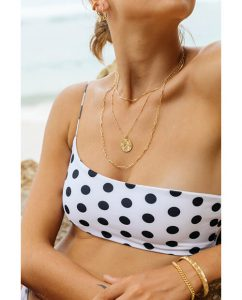 シンプルな18kゴールドメッキのネックレスを重ね付けした海辺にいるビキニの女性