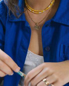 黄色と白のビーズがキュートなネックレスをつけた女性