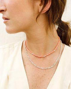 コーラルピンクとピンクのビーズがキュートなネックレスをつけた女性