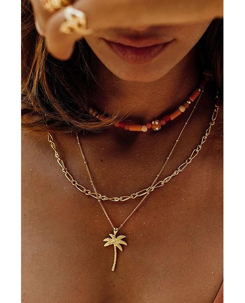 海辺にいるゴールドのアクセサリーを身につけたビキニの女性のアップ