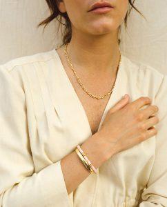 シンプルだけどインパクトのあるゴールドのネックレスをつけた女性