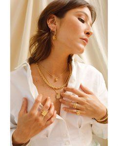 ヴィンテージピーチのペンダントトップのネックレスをつけた女性