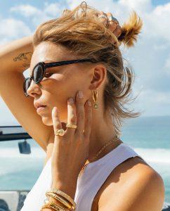 海辺でお花モチーフパターンの18kゴールドメッキリングをつけた女性