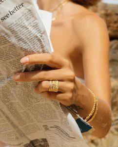 お花モチーフパターンの18kゴールドメッキリングを重ねづけした女性