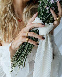 お花モチーフパターンの18kゴールドメッキリングをつけた女性