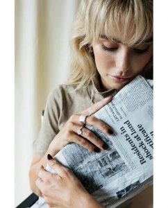 大ぶりなシルバー925のリングをつけた新聞を読む女性