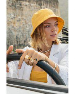車を運転するゴールドのアクセサリーをつけた女性