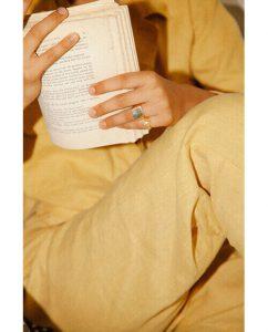 ゴールドアクセサリーをつけた女性が本を読む
