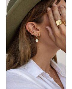 ゴールドの指輪やピアスをつけた女性