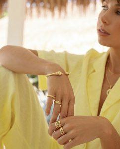 カラーストーンを埋め込んだ18kゴールドメッキのリングを重ね付けした女性