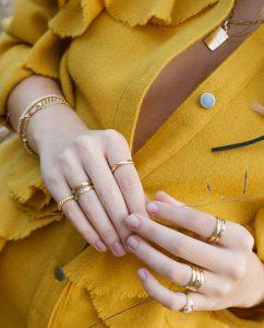 カラーストーンを埋め込んだ18kゴールドメッキのリングをつけた女性