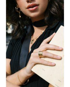 シトリンカラーのストーンを埋め込んだゴールドのリングをつけた女性