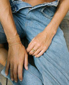 幅広いコーディネートに合うゴールドのシンプルなブレスレットをつけた女性の手