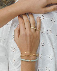 シンプルでかわいい淡いグリーンのビーズブレスレットをつけた女性の手