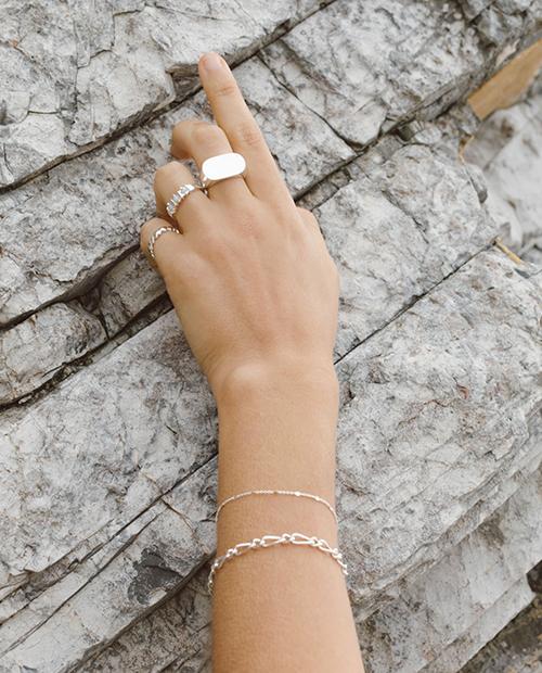 程良い存在感のシンプルなシルバー925のチェーンブレスレットをつけた女性の手