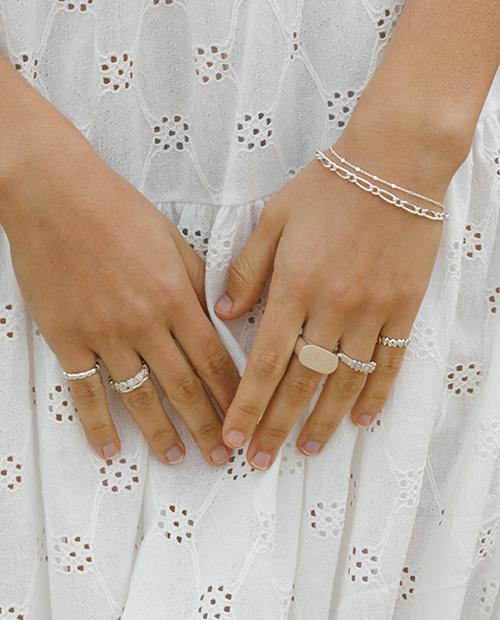 程良い存在感のシンプルなシルバー925のチェーンブレスレットをつけた女性の手のアップ