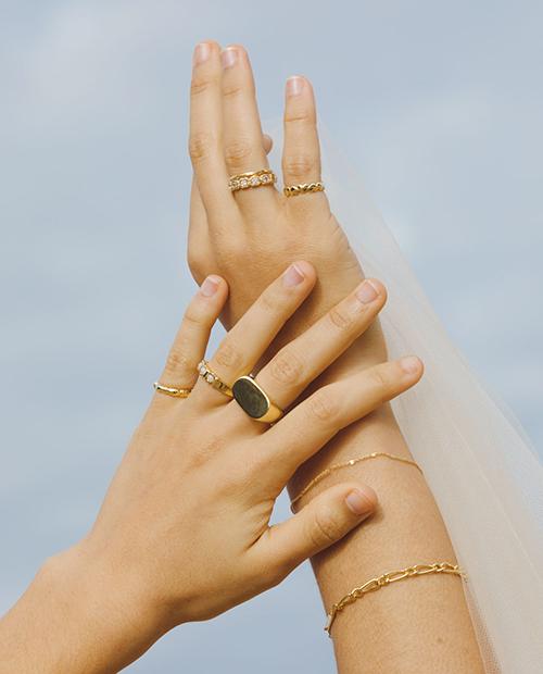 程良い存在感のシンプルなゴールドのチェーンブレスレットをつけた女性の手