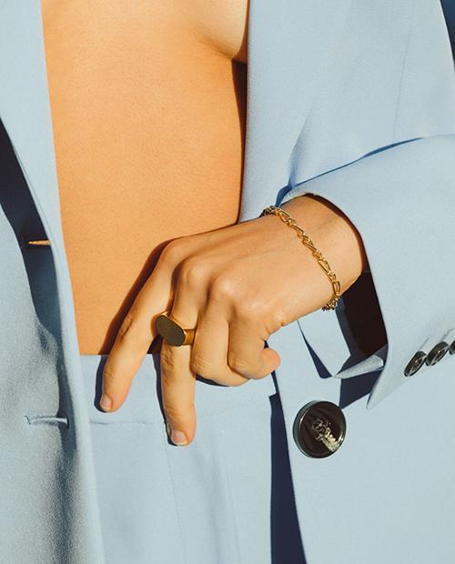 程良い存在感のシンプルなゴールドのチェーンブレスレットをつけた女性の手のアップ