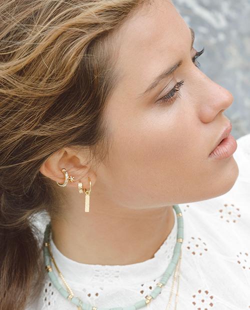 ピアスホールのいらない星がモチーフのイヤーカフゴールドをつけた女性の横顔