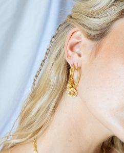 シンプルなゴールドのミディアムサイズのフープピアスをつけた女性のアップ