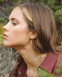 淡いグリーンのアイススターがキュートなゴールドの小ぶりなフープピアスをつけた女性の横顔