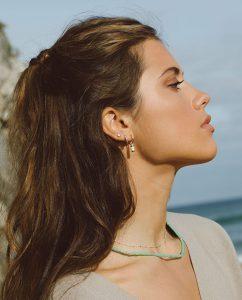 エメラルドグリーンの海を思わすビーズのネックレスをつけた女性と海