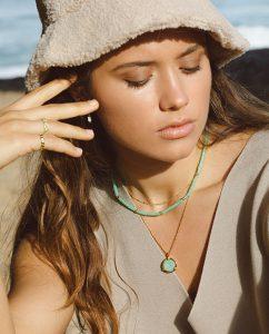 エメラルドグリーンの海を思わすビーズのネックレスをつけた女性