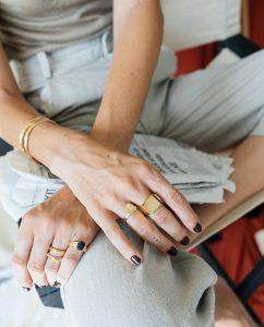 メンズライクな竹モチーフのシンプルなゴールドのリングをつけた女性のアップ