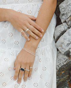 指先をひときわ輝かせる華やかなシルバー925のリングをつけた女性の手のアップ