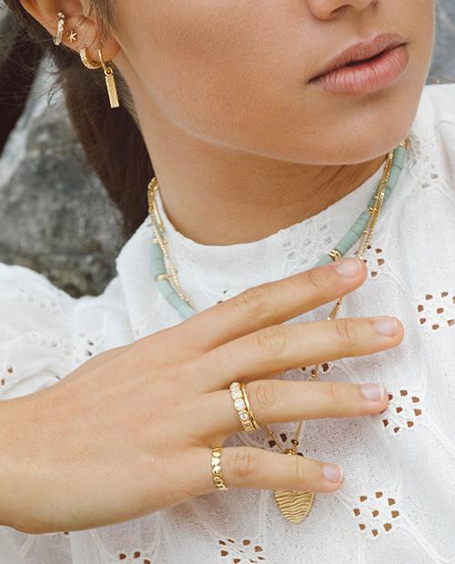 指先をひときわ輝かせる華やかなゴールドのリングをつけた女性の手