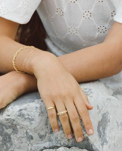 シンプルで華奢な細めのゴールドのリングの女性の手